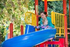 有妈妈的愉快的可爱的女孩在操场的儿童的幻灯片的在幼儿园蒙台梭利附近 库存照片