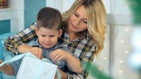 有妈妈的愉快的小男孩开放圣诞节礼物盒 股票录像