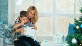 有妈妈的愉快的小男孩开放圣诞节礼物盒 影视素材