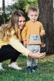 有妈妈的男孩喂养鸽子 免版税库存照片