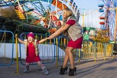 有妈妈的滑稽的小女孩获得乐趣在游乐园 免版税图库摄影