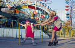 有妈妈的滑稽的小女孩获得乐趣在游乐园 免版税库存图片