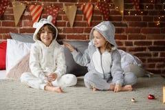 有姐妹的兄弟坐床并且期待圣诞节礼物 免版税图库摄影