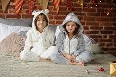 有姐妹的兄弟坐床并且期待圣诞节礼物 库存照片