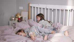 有姐妹的愉快的逗人喜爱的女儿和母亲有说谎在一张桃红色床上的枕头战并且获得乐趣在舒适轻的卧室 股票录像