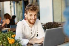 有姜头发和胡子的,微笑年轻悦目欧洲人,看与愉快和激动的表示的照相机 库存图片