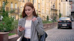 有姜头发的年轻美丽的妇女走在城市和看她的电话,黄色大厦背景的 股票视频