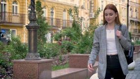 有姜头发的看起来年轻确信的妇女走在城市和向前,黄色大厦背景 股票录像