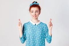 有姜头发和俏丽的面孔横穿手指的迷信少年女孩好运的,希望她愿望将实现, hav 库存图片