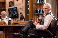 有威士忌酒玻璃和雪茄的典雅的老人在理发店 库存图片