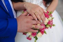 有婚戒的新娘和新郎的手在花 库存照片