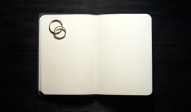 有婚戒的空白的笔记本在黑背景 库存图片