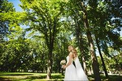 有婚礼发型的美丽的白肤金发的式样女孩,在长的白色礼服在公园走并且摆在与 免版税库存图片