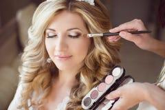 有婚礼构成和发型的美丽的新娘女孩 美发师 库存图片
