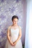 有婚礼构成和发型的美丽的年轻新娘在卧室 与面纱的美丽的新娘画象在她的面孔 特写镜头 免版税库存图片