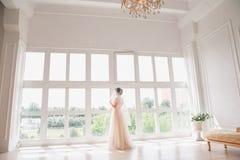 有婚礼构成和发型的美丽的年轻新娘在卧室 与面纱的美丽的新娘画象在她的面孔 特写镜头 库存照片