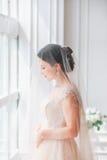 有婚礼构成和发型的美丽的年轻新娘在卧室 与面纱的美丽的新娘画象在她的面孔 特写镜头portr 库存照片