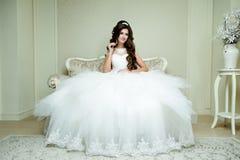 有婚礼构成的美丽的深色的典雅的与金刚石的新娘和发型加冠坐在葡萄酒扶手椅子 免版税库存照片