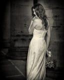 有婚礼的新娘开花在白色礼服的花束有婚礼发型和构成的 等待gr的婚礼礼服的微笑的妇女 免版税库存图片
