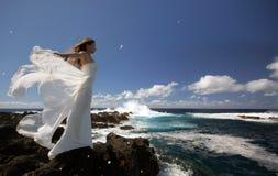 有婚礼礼服白色翼的年轻未婚妻在岩石海岸的在圣地米格尔海岛,亚速尔群岛上 免版税图库摄影