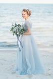 有婚礼花束的华美的新娘由海 库存照片