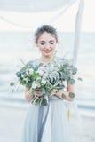 有婚礼花束的华美的新娘由海 免版税图库摄影