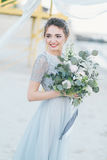 有婚礼花束的华美的新娘由海 免版税库存图片