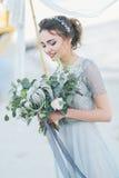 有婚礼花束的华美的新娘由海 库存图片