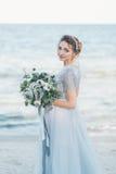 有婚礼花束的华美的新娘由海 免版税库存照片