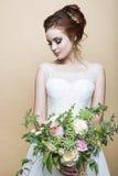 有婚礼花束的年轻俏丽的新娘 免版税库存图片