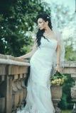 有婚礼花束的新娘在阳台 时尚白色礼服和面纱的新娘 免版税图库摄影