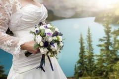 有婚礼花束的新娘由湖 免版税库存照片
