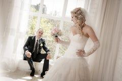 有婚礼花束的新娘从玫瑰和坐在窗口的新郎 库存图片