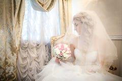 有婚礼花束的新娘从玫瑰在手上坐沙发在窗口附近 库存照片