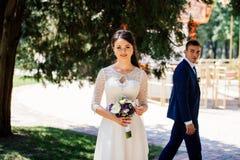 有婚礼花束的美丽的年轻新娘与背景的新郎 免版税库存照片