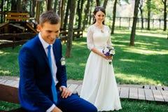 有婚礼花束的美丽的年轻新娘与迷离的新郎在她前面 在爱的夫妇婚礼之日 库存照片