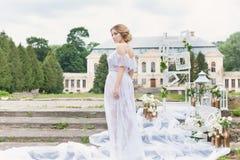 有婚礼花束的美丽的年轻甜白肤金发的女孩在闺房的手上一件白色礼服的有晚上发型的走 免版税库存图片