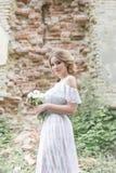 有婚礼花束的美丽的年轻甜白肤金发的女孩在闺房的手上一件白色礼服的有晚上发型的走 图库摄影