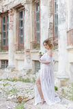 有婚礼花束的美丽的年轻甜白肤金发的女孩在闺房的手上一件白色礼服的有晚上发型的走 免版税库存照片