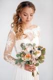 有婚礼花束的年轻可爱的新娘 免版税库存照片