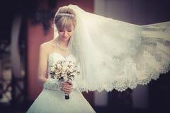 有婚礼bouqet的美丽的白肤金发的新娘在手上 免版税库存图片