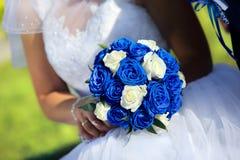 有婚姻的蓝色玫瑰花束的新娘户外 免版税库存图片