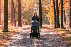 有婴儿推车的一个年轻母亲通过秋天公园走 免版税库存图片