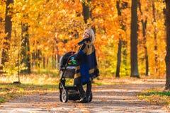 有婴儿推车的一个年轻母亲通过秋天公园走 库存照片