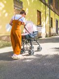 有婴儿推车的母亲在镇里 免版税库存图片