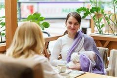 有婴儿的年轻欧洲快乐夫妇或朋友妇女坐接近白色婴儿车的长凳,当他们中的一个breastfe时 免版税库存照片