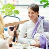 有婴儿的年轻欧洲快乐夫妇或朋友妇女坐接近白色婴儿车的长凳,当他们中的一个breastfe时 库存图片