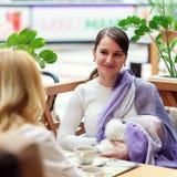 有婴儿的年轻欧洲快乐夫妇或朋友妇女坐接近白色婴儿车的长凳,当他们中的一个breastfe时 免版税图库摄影