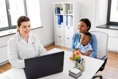 有婴孩和医生的母亲有在诊所的膝上型计算机的 免版税库存图片