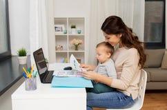 有婴孩的在家运作母亲和的文件 免版税库存照片